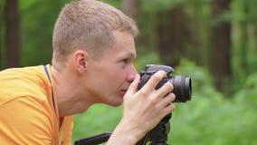 Ein junger Mann justiert Fokus auf einer Spiegelkamera und macht ein Foto stock video footage