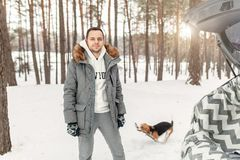 Ein junger Mann kleidete in einem grauen Winterpark in einem Wald des verschneiten Winters mit Spürhund an Konzept über Winterfre stockfotografie