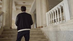 Ein junger Mann klettert die Treppe und macht Fotos einer verlassenen Villa stock footage