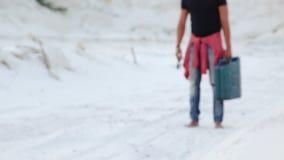 Ein junger Mann läuft die Wüste mit einem Kanister des Benzins auf der Suche nach Brennstoff durch stock footage