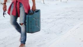 Ein junger Mann läuft die Wüste mit einem Kanister des Benzins auf der Suche nach Brennstoff durch stock video