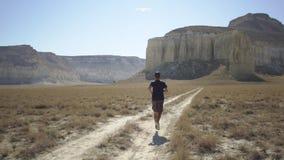 Ein junger Mann läuft mitten in einem Berggebiet stock footage