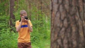 Ein junger Mann macht ein Foto auf einer Spiegelkamera im Wald stock footage
