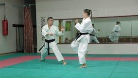 Ein junger Mann mit übenden Kampfkünsten Goju-Ryu eines muskulösen Körpers und einer Frau Karate-tun Superzeitlupe stock video