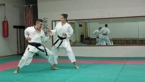 Ein junger Mann mit übenden Kampfkünsten Goju-Ryu eines muskulösen Körpers und einer Frau Karate-tun Superzeitlupe stock video footage
