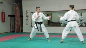 Ein junger Mann mit übenden Kampfkünsten Goju-Ryu eines muskulösen Körpers und einer Frau Karate-tun Superzeitlupe stock footage