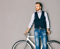 Ein junger Mann mit dem Schnurrbart und Bart ist nahe modernem modernem fixgear Fahrrad Jeans und Hemd, Weste und das Fliegenhipp stockfotografie