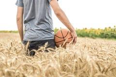 Ein junger Mann mit einem Basketball auf der Natur, Konzept des Sports stockfoto