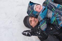 Ein junger Mann mit einem netten Jungen mit einer Achterbahnfahrt im Th Stockbild