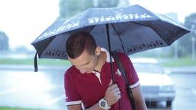 Ein junger Mann mit einem Regenschirmlächeln stock video footage