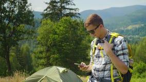 Ein junger Mann mit einem Rucksackgebrauch ein Smartphone im Kampieren Immer in der Note, Anwendungen für Tourismus stock video
