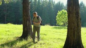 Ein junger Mann mit einem Smartphone sucht nach Richtung in den Wald stock footage