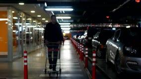 Ein junger Mann mit einem Warenkorb geht auf ein Untertageautoparken für den Einkauf in einem Einkaufszentrum, Konzept stock video