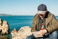 Ein junger Mann oder ein Tourist benutzt eine Tablette, die auf der Atlantikküste sitzt stockbild