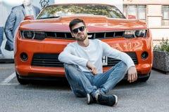 Ein junger Mann reist durch die Straßen der Stadt Junge im stilvollen Mann der Sonnenbrille nahe dem Gebäude Der Mann sitzt auf a stockfotografie