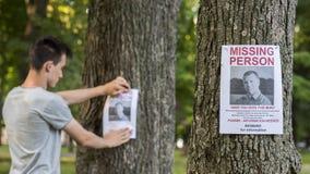 Ein junger Mann setzt oben Anzeigen für eine vermisste Person in den Park ein lizenzfreies stockbild