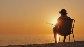 Ein junger Mann sitzt auf der Küste und fischt Im Freien sich entspannen Stockfotografie