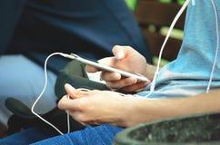 Ein junger Mann sitzt auf der Straße und benutzt einen Smartphone mit Kopfhörern lizenzfreies stockbild