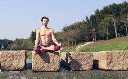 Ein junger Mann sitzt auf einem Stein im Lotussitz auf dem Hintergrund des Flusses im Park Stockfoto