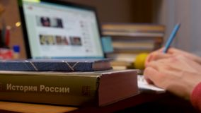 Ein junger Mann sitzt an einem Tisch und schreibt in ein Notizbuch stock video