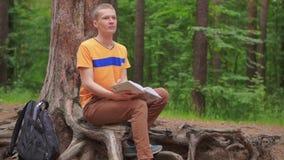 Ein junger Mann sitzt im Wald und liest ein Buch stock footage