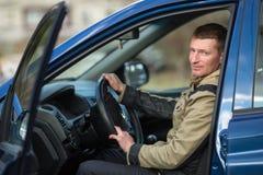 Ein junger Mann sitzt in seinem Neuwagen liebhaberei lizenzfreie stockfotos