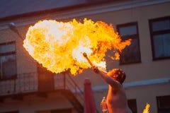 Ein junger Mann spuckt ein Feuer aus seinem Mund heraus stockfotografie