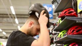 Ein junger Mann steht nahe einem Stand in einem Fahrradladen W?hlen eines Fahrradsturzhelms in einem kleinen Speicher stock footage