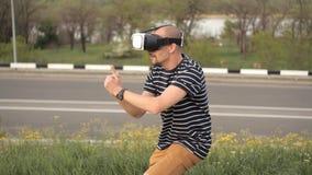 Ein junger Mann steht vor Natur in einem Sturzhelm der virtuellen Realität Tauchenspiele oder panoramisches Video - der Film, der stock video footage
