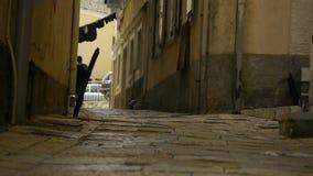 Ein junger Mann strebt eine Drehung auf einer schmalen Straße an stock video footage