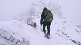 Ein junger Mann, ein Tourist, mit einem Rucksack auf seinen Schultern steigt auf der Spitze eines schneebedeckten Berges stock video