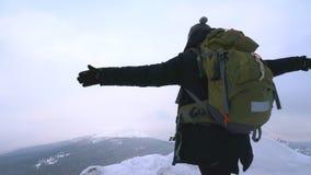 Ein junger Mann, ein Tourist, steht am Rand eines schneebedeckten Berges und bewundert die Spitze des Berges stock video footage