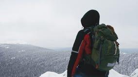 Ein junger Mann, ein Tourist, steht am Rand eines schneebedeckten Berges und bewundert die Spitze des Berges stock video