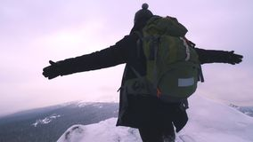 Ein junger Mann, ein Tourist, steht am Rand eines schneebedeckten Berges und bewundert die Spitze des Berges stock footage