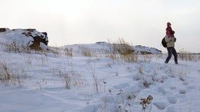 Ein junger Mann trägt ein Kind in seinen Armen auf einem schneebedeckten Hügel, den ein Blizzard anfängt stock video