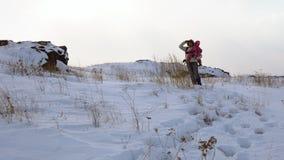 Ein junger Mann trägt ein Kind in seinen Armen auf einem schneebedeckten Hügel, den ein Blizzard anfängt stock footage