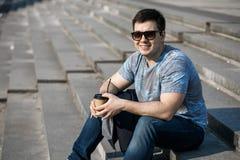 Ein junger Mann trinkt Kaffee in der Stadt und in den Wegen draußen lizenzfreie stockfotos