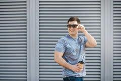 Ein junger Mann trinkt Kaffee in der Stadt und in den Wegen draußen lizenzfreie stockfotografie