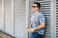 Ein junger Mann trinkt Kaffee in der Stadt und in den Wegen draußen stockfoto