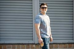 Ein junger Mann trinkt Kaffee in der Stadt und in den Wegen draußen lizenzfreies stockfoto