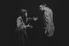 Ein junger Mann und eine Frau, welche die Rolle des Spiels auf einem dunklen Hintergrund spielen Stockfoto