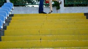 Ein junger Mann und eine Schönheit, welche oben die Treppe - Küssen von Liebhabern laufen lassen stock footage