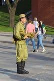 Ein junger Mann verkauft Militärandenken nahe dem Moskau der Kreml Stockfotografie