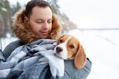 Ein junger Mann wickelte seinen bester Freund Spürhundhund in einer warmen Decke ein, um ihn in einem kalten verschneiten Winter  lizenzfreie stockfotos