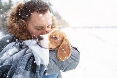 Ein junger Mann wickelte seinen bester Freund Spürhundhund in einer warmen Decke ein, um ihn in einem kalten verschneiten Winter  lizenzfreies stockbild