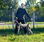 Ein junger Mann zeigt einen dalmatinischen Hund Lizenzfreie Stockbilder