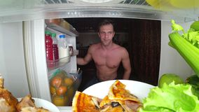 Ein junger muskulöser Mann öffnet den Kühlschrank nachts Nachthunger Diät gluttony lizenzfreies stockfoto
