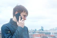Ein junger netter Mann, der auf einem tragbaren Gerät spricht stockfoto