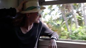 Ein junger netter Mann reist mit dem Zug in Sri Lanka stock footage