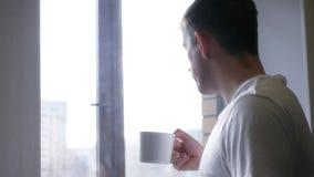 Ein junger netter Mann trinkt von einer weißen Schale, von einem Tee oder von einem Kaffee 4k, 3840x2160 HD stock footage